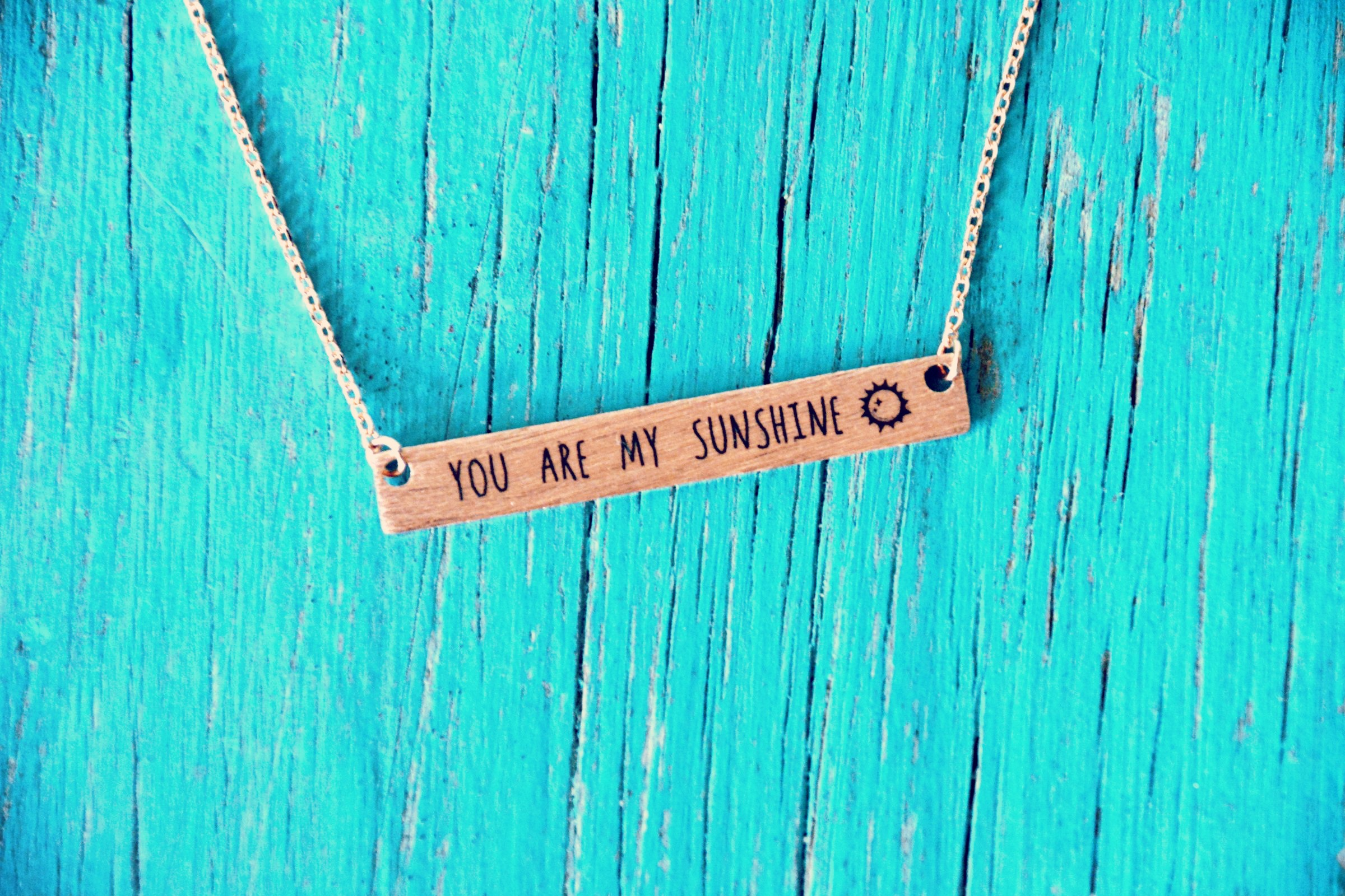 Fine chain necklace in a rose gold style finish, with a flat bar engraved with 'You are my sunshine' and a little sun picture.